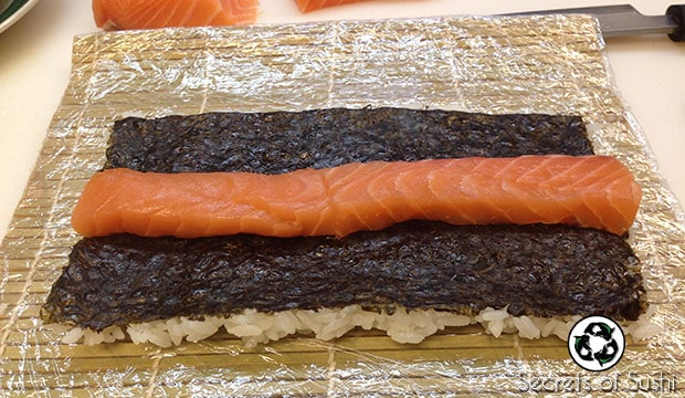 Placing sliced salmon on Paleo Sushi