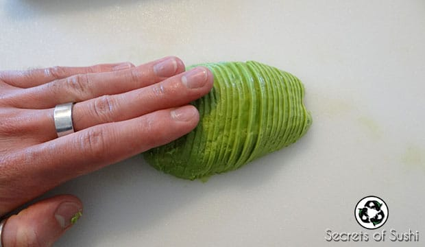pushing sliced avocado