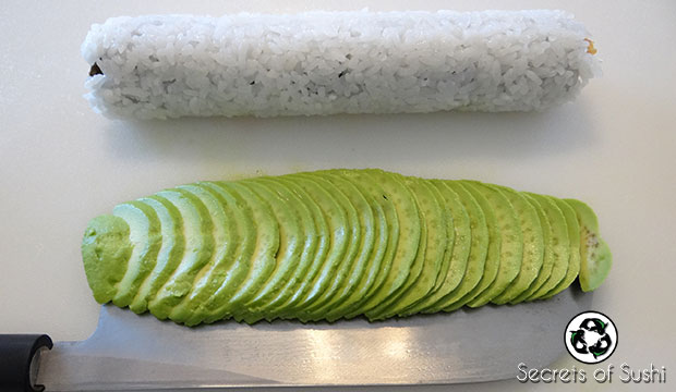 transferring avocado to a caterpillar roll
