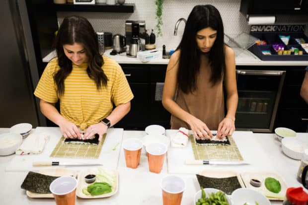 Two women making sushi at a party